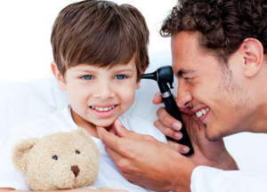 The doctor examines the ear of the child