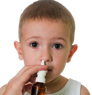 Boy using nose spray