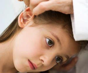 Доктор капает капли в уши ребенка