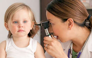 The doctor checks the hearing of a child