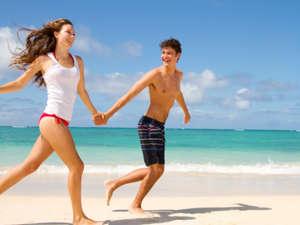 The guy and the girl run on the beach