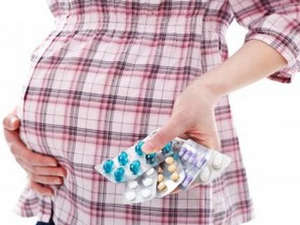 Pills in the hands of a pregnant