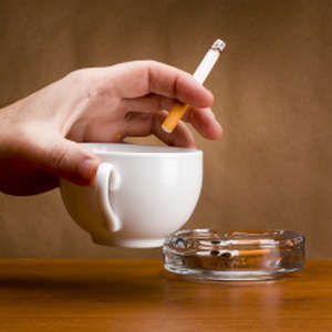 Cup with a cigarette in hand