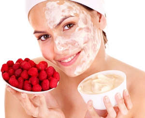 Applying cream with berries on the face