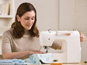 Женщина делает двойной шов на машинке
