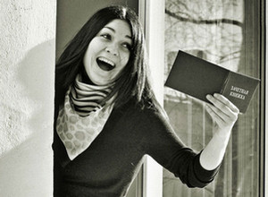Girl waving a record book from the window