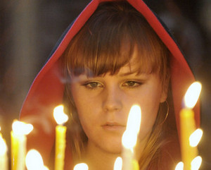 Девушка в красном капюшоне перед свечами