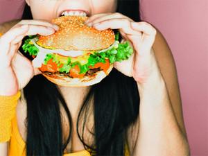 Девушка ест гамбургер