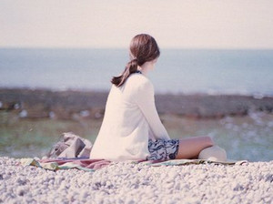 The girl sits alone and looks into the distance