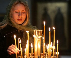 The girl puts a candle in the church