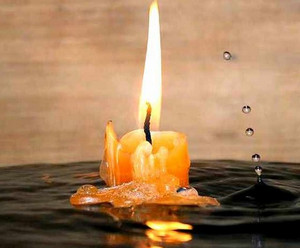 Burning candle on the water