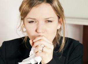 Девушка в черном свитере кашляет