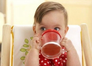 Baby is drinking from a mug