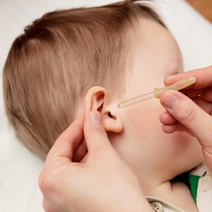 The instillation of medicine in the ear of the baby