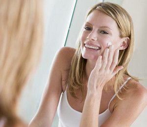 The girl puts cream in front of the mirror