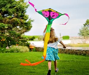 Девочка бежит с воздушный змеем в руках