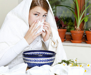 The girl with a white towel on her head makes inhalation from a cold