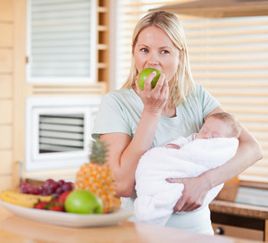 A girl with a baby in her arms is eating an apple