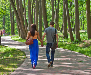 The guy and the girl walk by the handle in the park