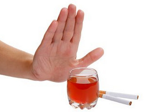 Hand in front of a glass with alcohol and cigarettes