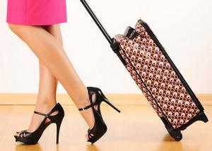 Woman on heels rolls a suitcase