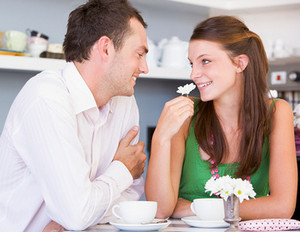 Woman sniffing a white flower and looking at a man