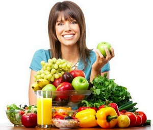 The girl sits at the table in front of a bunch of vegetables and fruits.