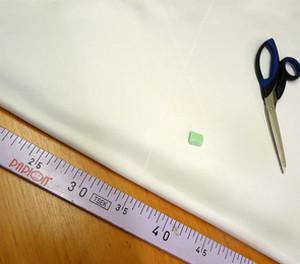 Сложенная белая ткань, сантиметр и ножницы