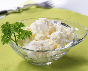 Cottage cheese in a glass plate on a green tablecloth