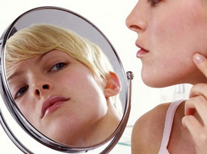 Woman examines herself in the mirror