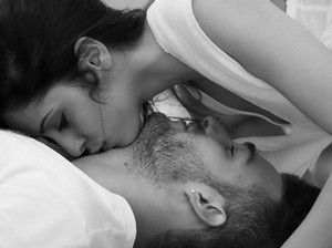 The girl kisses the man in the neck