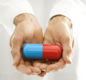 Red and blue pill in hand