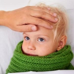 Мама измеряет температуру рукой мальчику в зеленом шарфе