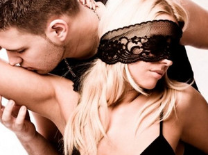 A man kisses the hand of a woman in a black lace band