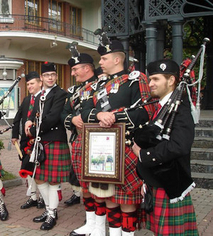 Scots in skirts with musical instruments