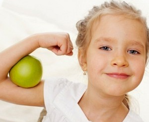 Healthy and happy girl squeezed green apple