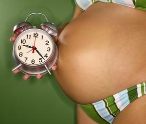 Беременная женщина с будильником в руках