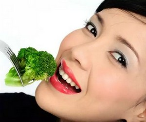 Girl eats broccoli with a fork