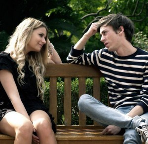 Young people sit on a bench and talk