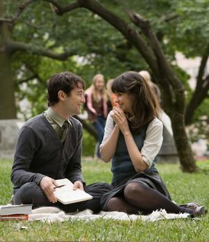 Парень с девушкой сидят на лужайке и мило беседуют