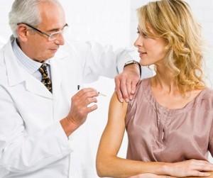 Врач делает прививку женщине