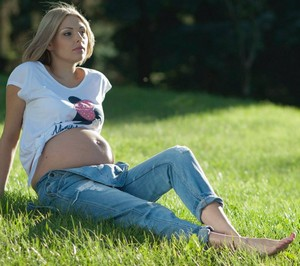 Pregnant girl sitting on the grass