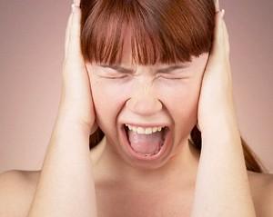 Девушка кричит и закрывает уши руками