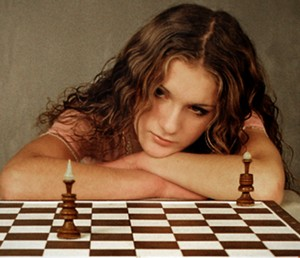 The girl leaned on the chessboard