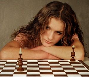 Девушка облокотилась на шахматную доску