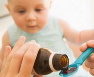 Мама наливает ребенку лекарство