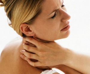 Woman holds hand on sore neck