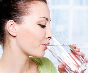 The girl drinks water from a glass