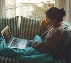 Girl under the covers with a cup is watching a movie on a laptop