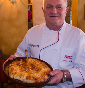 Cook holds dish with khachapuri
